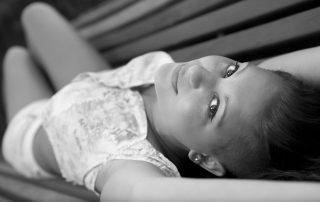 chica tumbada en banco, mirando a cámara