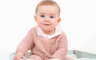 bebé sonriente con ojos azules y pelo rubio